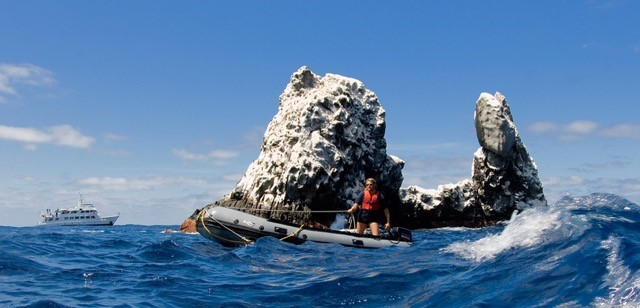 skiff operator with sunglasses passes by roca partida and the nautilus explorer