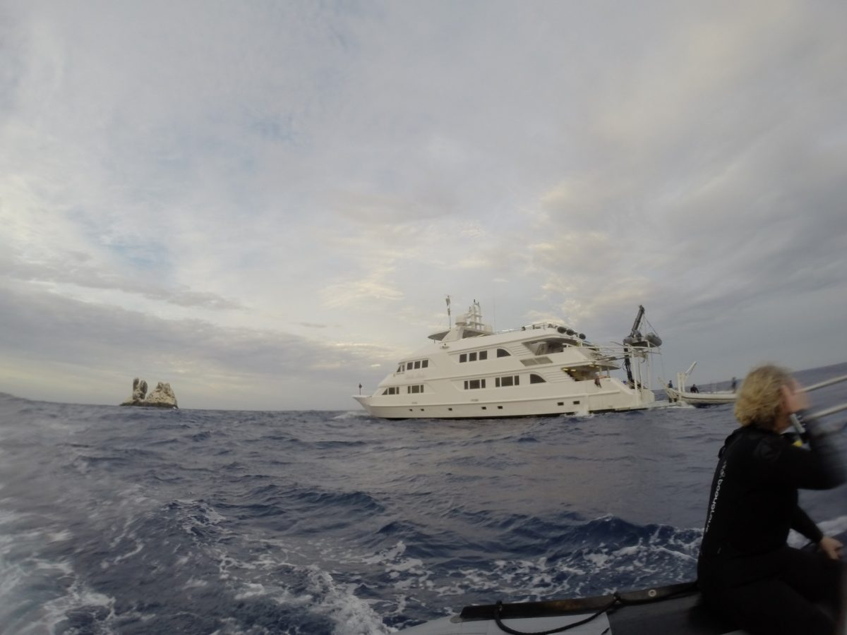 divers in a skiff, the nautilus belle amie, and roca partida in the distance